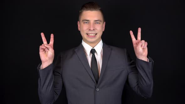 Thumbnail for Young Businessman Shows a Victory Sign with Two Hands. Man in a Black Suit on a Black Background