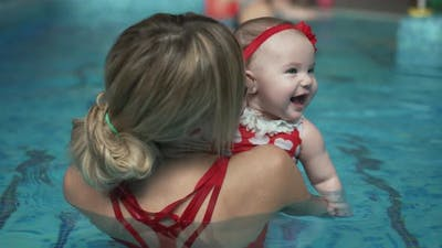 Happy Mother with a Baby in the Pool