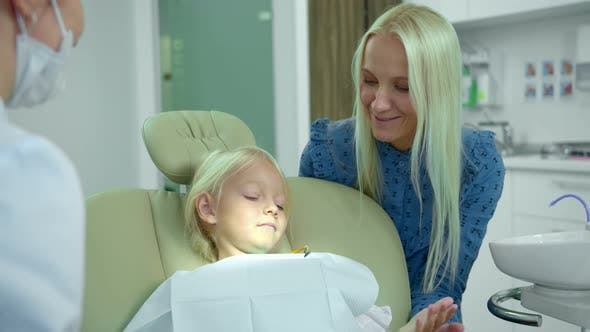 Cover Image for Mother Sits with Her Daughter and Talks To Dentist