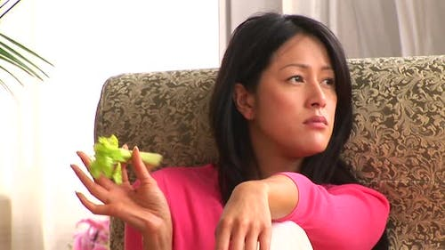 Young woman eating celery