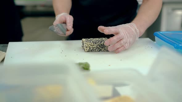 Thumbnail for Cook Cuts a Japanese Roll with Sesame Seeds.
