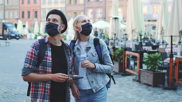 Tourists in Protective Masks and with Bags Using Smartphone