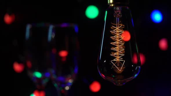 Two Glasses Champagne Are Are Lit Against the Background of Light Bulbs Flashy Flashlights