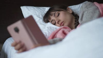 Sad Woman Lying in a Bed and Uses Smartphone