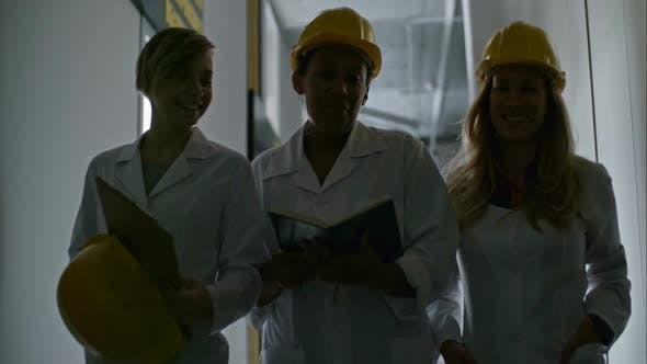 Thumbnail for Female Engineers Walking through Corridor, Chatting and Laughing