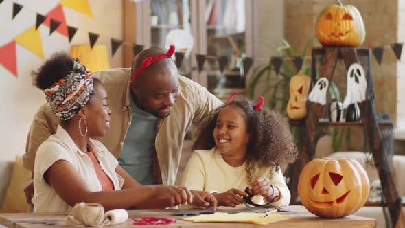 Thumbnail for Happy Afro-American Family Making Halloween Decorations at Home