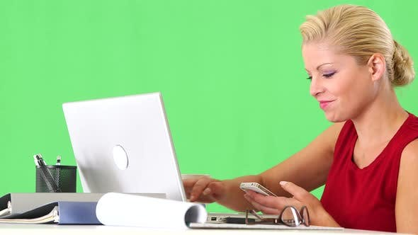 Thumbnail for Businesswoman working with cellphone and laptop at desk