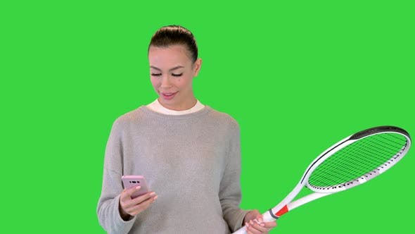 Pretty Young Female Tennis Player Walking and Using Smart Phone on a Green Screen Chroma Key