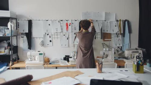Female Clothes Designer Looking at Drawings of Garments Hanging on Wall