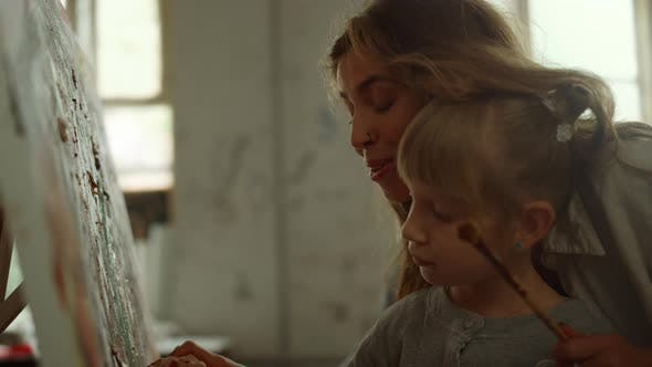 Smiling Mother Holding Daughter Hand in Workshop