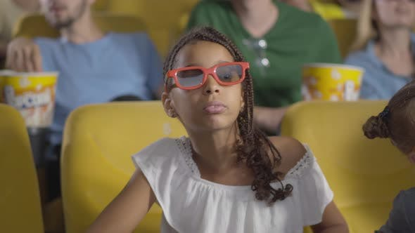 Cheerful Excited African American Girl with Afro Pigtails Moving To 3d Film in Cinema. Portrait of