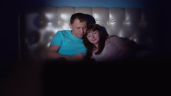 Night a Couple Lies on the Bed in Front of the TV Man Feeds a Woman with Ice Cream and Eats