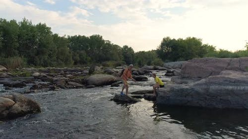 Couple Skimming Stones Across a River