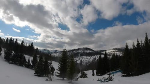 Timelapse clouds floating the sky. Snowed hills and mountains. Winter time.
