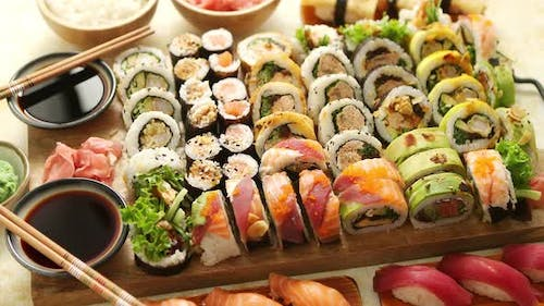 Above View of Various Sushi and Rolls Placed on Wooden Board. Japanese Food Fest