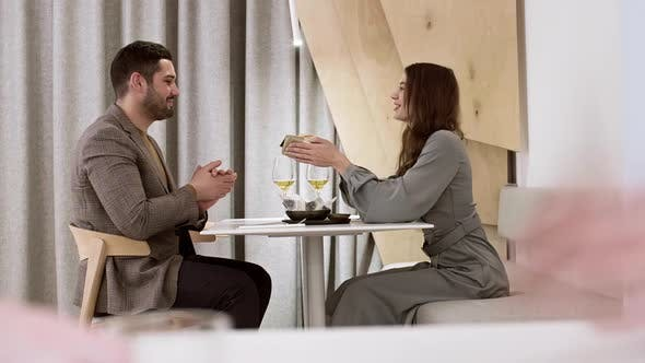 Man Receiving Present from Wife in Cafe
