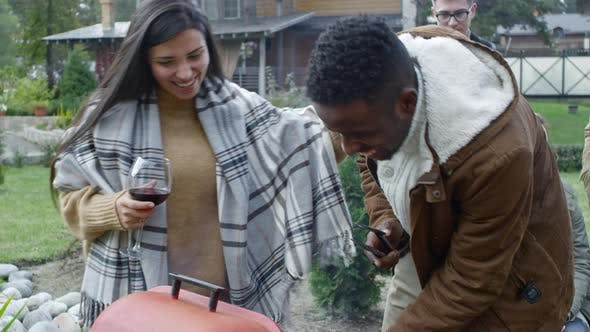 Joyous Man and Woman Cooking on Grill at Outdoor Party