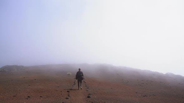 Thumbnail for Man Walking Along Stony Ground Under Misty Sky