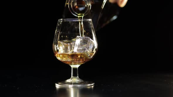 Thumbnail for Pouring Whiskey, Cognac Into Glass. Black Background. Pour of Alcohol Drink