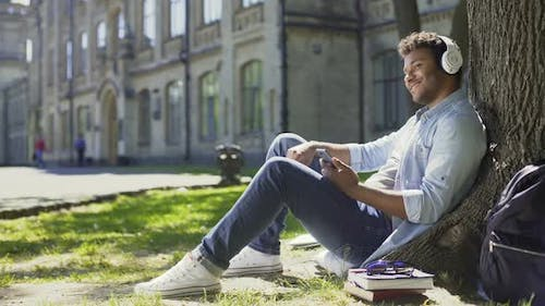 Male in Headphones Sitting on Grass and Leaning Against Tree, Listening to Music
