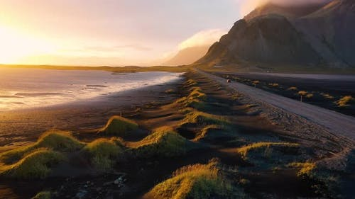 Flying Over a Dirt Road at Sunset with Vestrahorn Mountain in Iceland