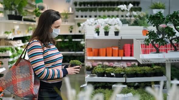 Frau in Schutzmaske Shopping für Pflanzen