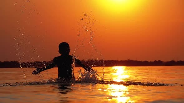 Cover Image for Silhouette of Boy at Sunset Raises Hands and Creating Splashes of Water. Slow Motion