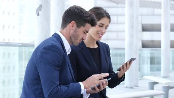 Thumbnail for Geschäftsmann und Geschäftsfrau mit Handy zusammen im Freien