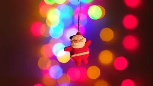 New Year Santa Claus Toy Hanging on a Background of Holiday Lights