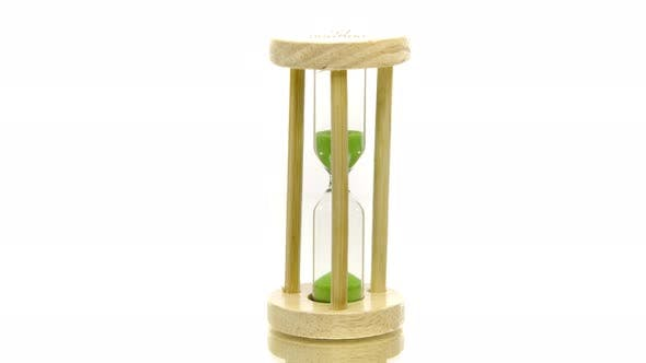 Green Sand Pouring in Hourglass Spinning 360 on White. Global Warming Deadline