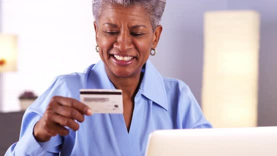 Thumbnail for Happy Mature Black woman typing in card information