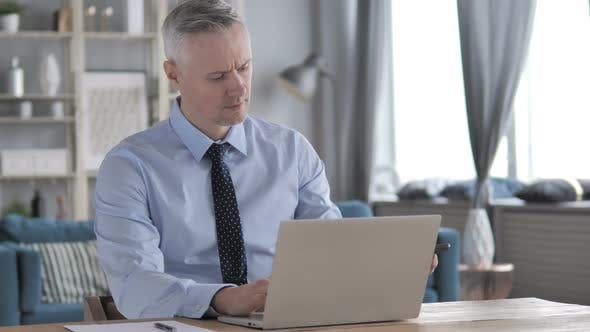 Thumbnail for Gray Hair Businessman Attending Phone Call While Working on Laptop