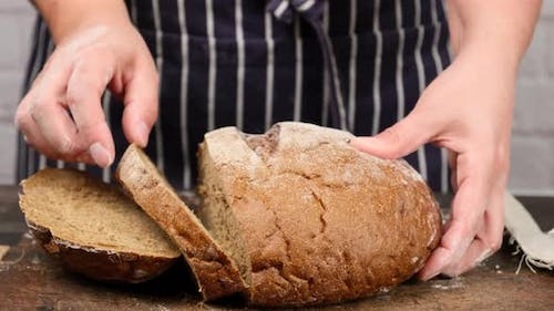 Woman In A Blue Apron Holds A Sliced Round Rye Bread