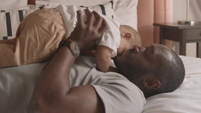 Father Kissing Son in Bed