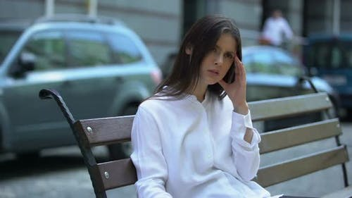 Müde Lady sitzt auf Bank, leidet unter Kopfschmerzen, meteorologische Abhängigkeit