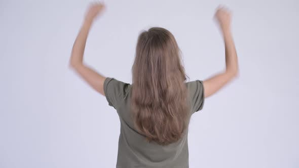 Rear View of Happy Young Woman with Fists Raised