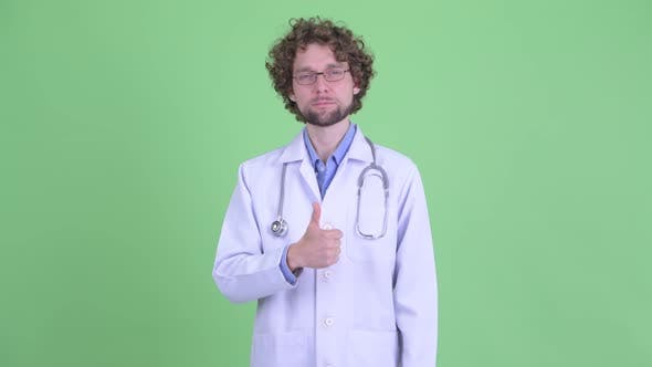 Cover Image for Happy Young Bearded Man Doctor Giving Thumbs Up
