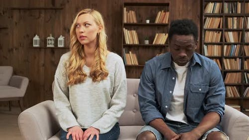Upset Mixed Race Ethnicity Young Couple Sit Separate Turn Back on Sofa Avoid Talk After Fight