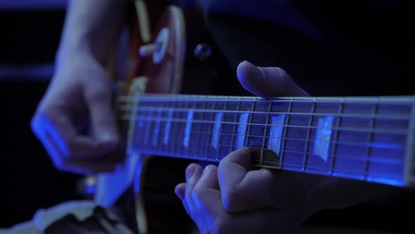 Guitarist playing solo on electric guitar at sound record studio.