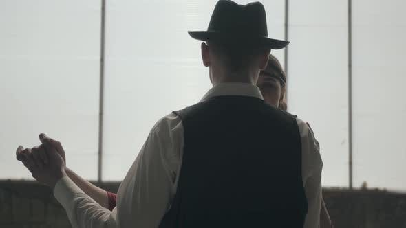 Thumbnail for Man in Fedora Hat, Classical Suits and Woman in Style Cloth Dancing in Dirty Place.