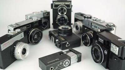 Zooming In On Old Film Cameras On A White Background 1.