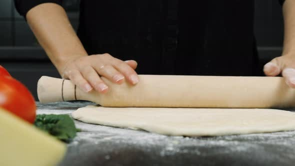 Hands are rolling out dough with rolling pin