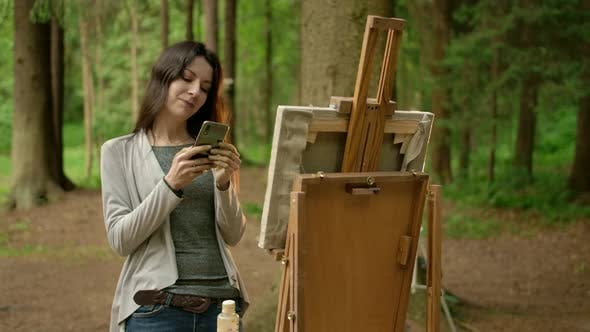 Thumbnail for Front Middle Frame of the Girl Artist with Cell Phone in a Park.