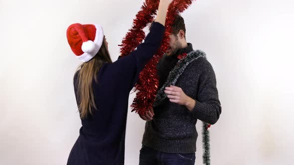 Thumbnail for A woman decorating a man with tinsel