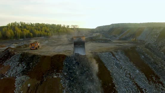 Thumbnail for Two Yellow Dump Trucks Unload the Ground