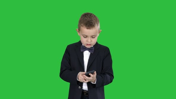 Thumbnail for Small boy in costume walking and using smartphone