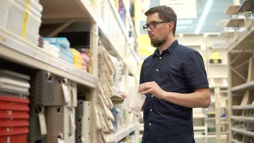 Householder is Comparing Two Plastic Boxes in Supermarket Standing Near Shelves