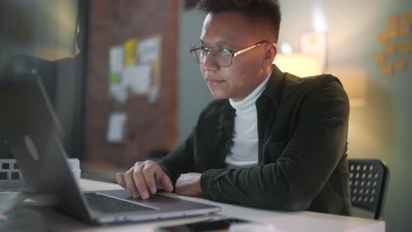 Thumbnail for Portrait Of a Man Is Working On Laptop Computer With Glasses At Night. Businessman Working Late At