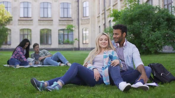 Thumbnail for Multiracial Couple Relaxing on Grass, Talking and Smiling, First Love, Students