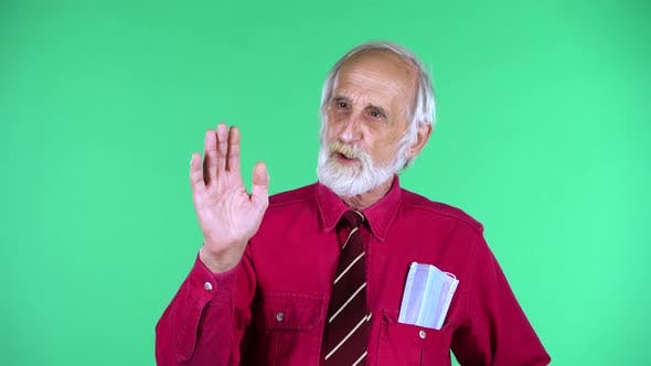 Cover Image for Portrait of Happy Old Aged Man 70s Communicates with Someone, Isolated Over Green Background.